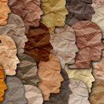 Paper cut out drawings of faces in profile are featured in various skin-tone shades.