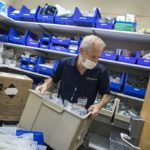 Stephen Caldwell, an inventory management specialist at Penn State Health Lime Spring Outpatient Center, lifts a box with medical supplies. He is wearing a polo shirt with the Penn State Health logo on it, a name badge and a face mask. Behind him are four shelves with supplies. Large plastic boxes are stacked to the left of him.