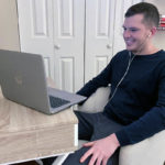 A man sits at a desk, wearing earbuds, looking at a laptop screen. He smiles slightly. A door, bookshelf and closet are in the background.