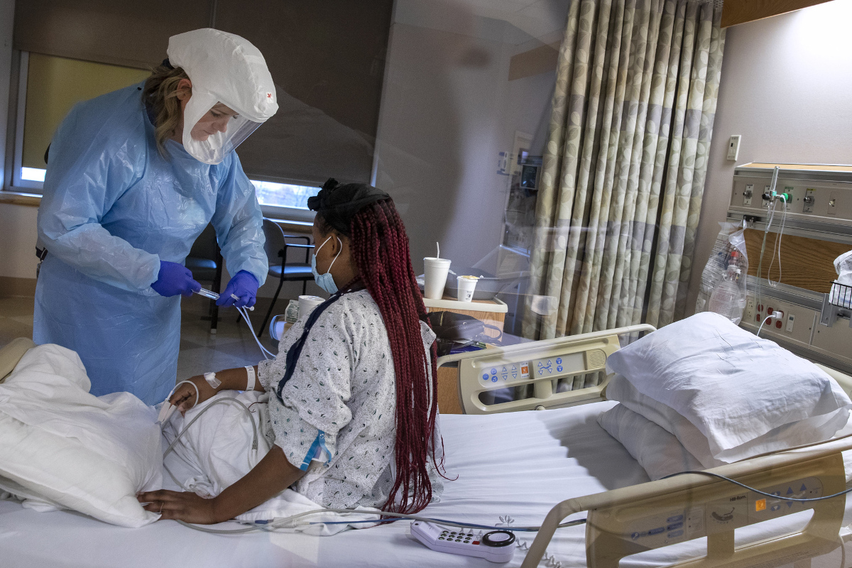 A female nursing assistant wearing full personal protective equipment stands at a patient's bedside, adjusting an IV line. The patient is sitting up in her bed, wearing a hospital gown. Other hospital equipment is throughout the room.