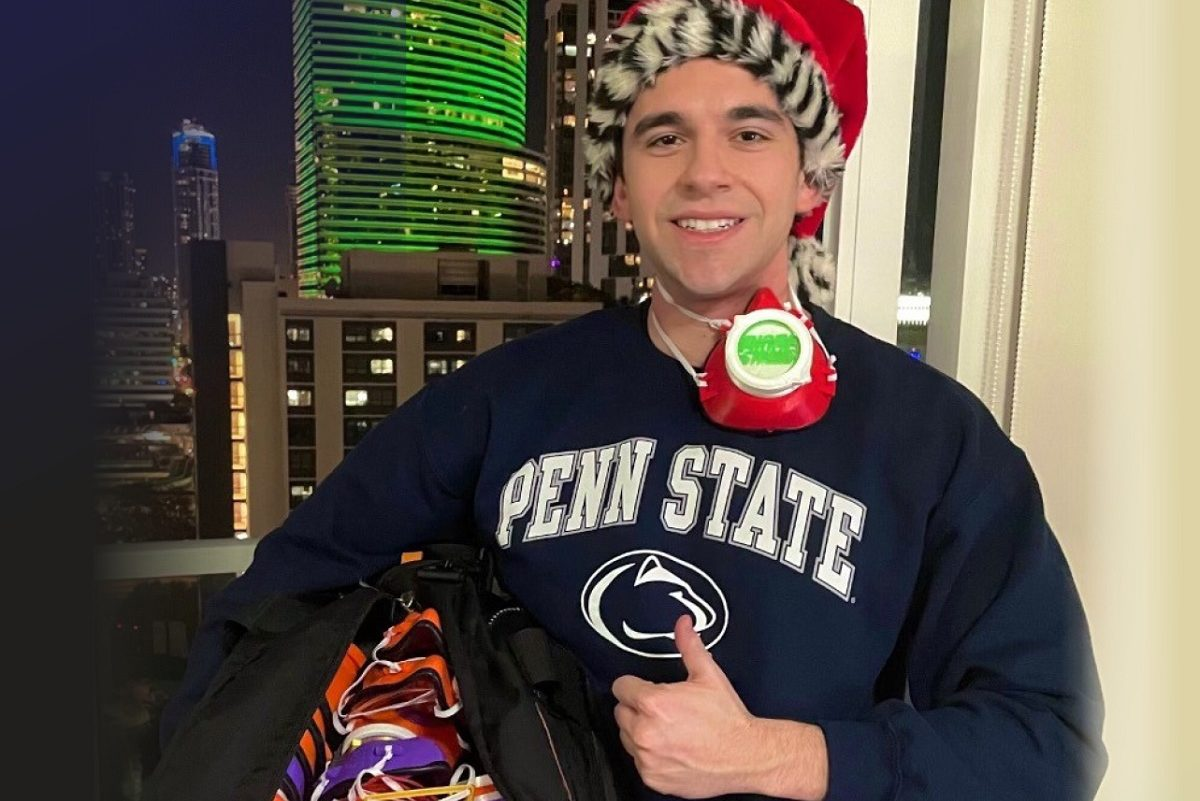 First-year College of Medicine medical student Marc Levine stands in front of a window at night wearing a Penn State T-shirt and Santa cap. He is giving the thumbs up and smiling. He has a face mask hanging from his neck and is holding a large bag with many face masks inside.