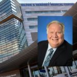 A head and shoulders portrait of Christopher Neidert against an image of Hershey Medical Center.