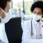 A Black woman doctor wearing a protective face mask talks to a male patient at a clinic. The doctor has a stethoscope around her neck and is sitting in a chair. The male patient is wearing a face mask and a button-down shirt.