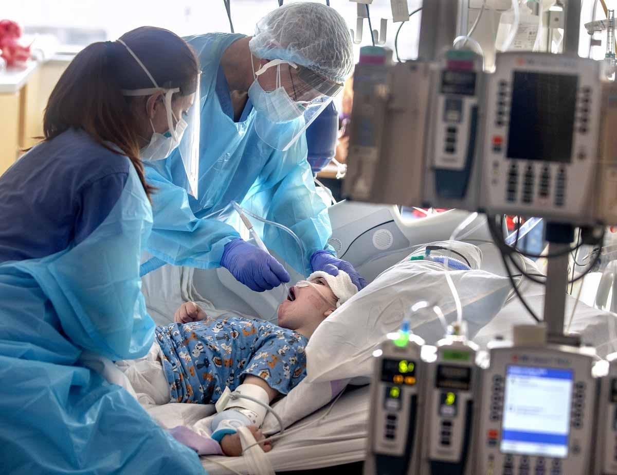 Dos trabajadores de la salud en equipo de protección personal deslizan un tubo por la garganta de un niño, mientras el niño descansa en una cama de hospital.