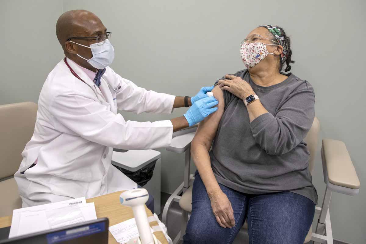 Un médico masculino que lleva un abrigo, estetoscopio, máscara facial y guantes de goma sostiene un vendaje contra el brazo de una paciente, quien sostiene la manga de su camisa.