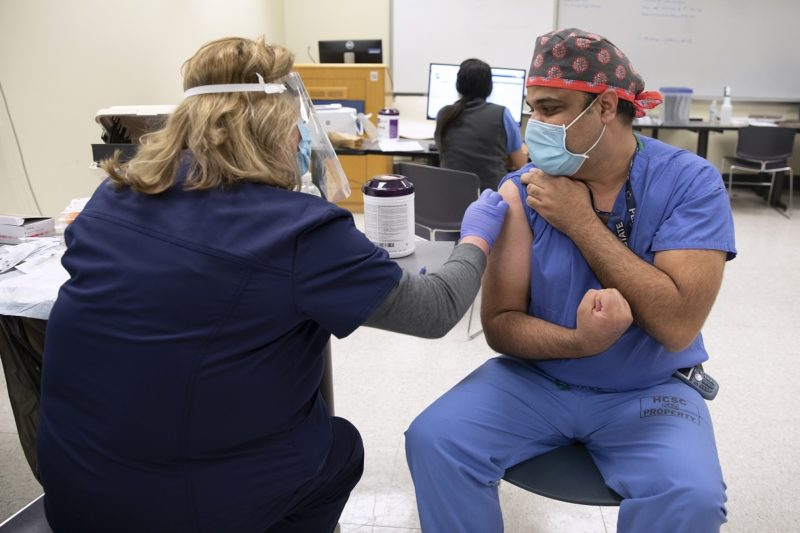 A man in scrubs, a head covering and a surgical masks, clenches his fist, while a woman in personal protective equipment prepares to give him a shot.