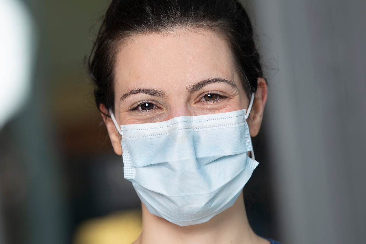 Close-up photo of a woman in a facemask, smiling.