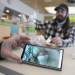 A hand holds a smart phone upon which is the image of an infant in a bed. Across a lunch table littered with bottles and food, a man with a beard and a hat looks on out of focus.