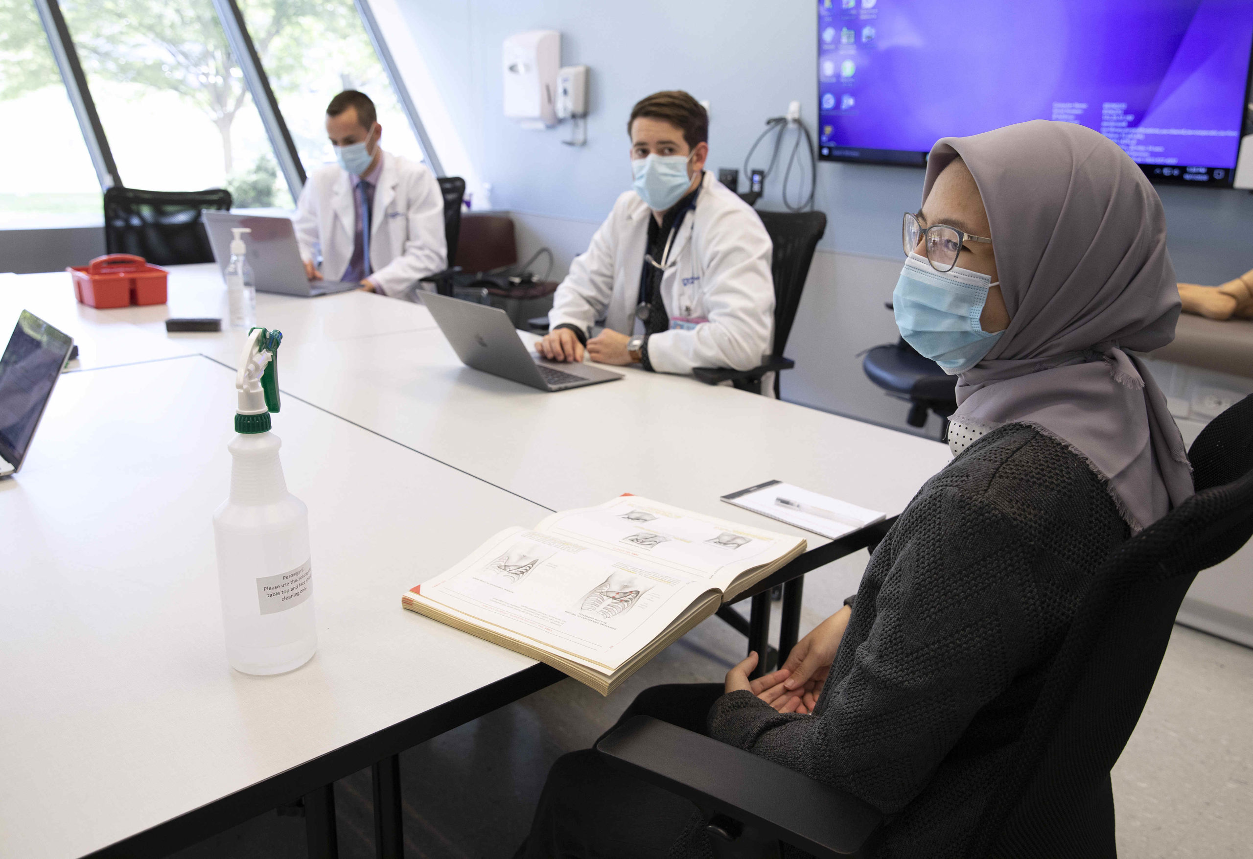 In the foreground, a female medical student wearing a surgical mask and head covering is seated at a conference table with an open textbook in front of her. In the background, two male students, also wearing surgical masks, are seated at adjoining conference tables with open laptops in front of them.