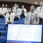 Ten students wearing white physician coats and masks stand in front of blue seats in Junker Auditorium. A large computer screen with details of the Student Clinician Ceremonies is set in front of the student seating.