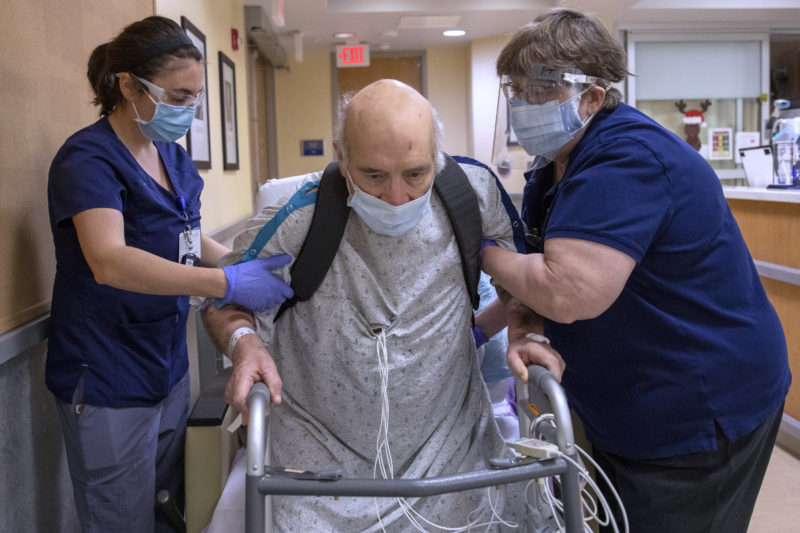 A man in a hospital gown rises out of a wheelchair to a standing position, leaning on a walker. Several wires emerge from his gown. Two staff members, one on each side, are bracing the man's upper arms.