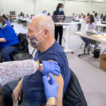A man wearing a face mask gets a vaccine in his left arm at a vaccine clinic