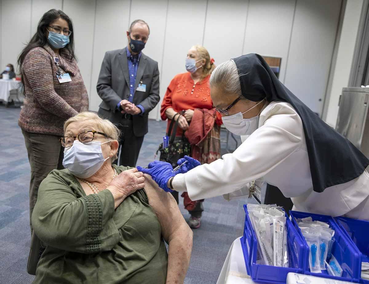 Una mujer con una máscara mira hacia otro lado mientras otra mujer con ropa del hospital, guantes de goma y el hábito de una monja le da una inyección en el hombro.
