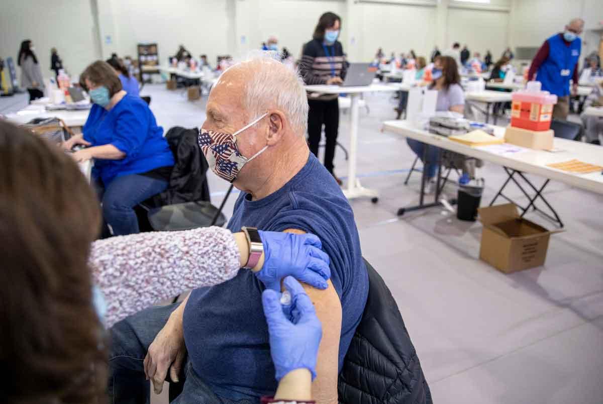 Un hombre con una máscara facial recibe una vacuna en su brazo izquierdo en una clínica de vacunas