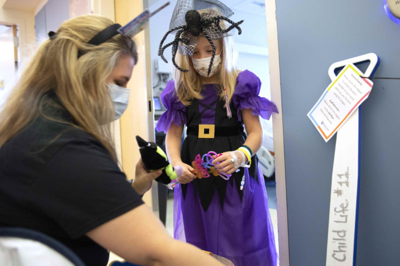 A young girl in a Halloween dress and spider hat stands in the doorway of a hospital room while a woman kneels down near her, holding up a doll-like toy.