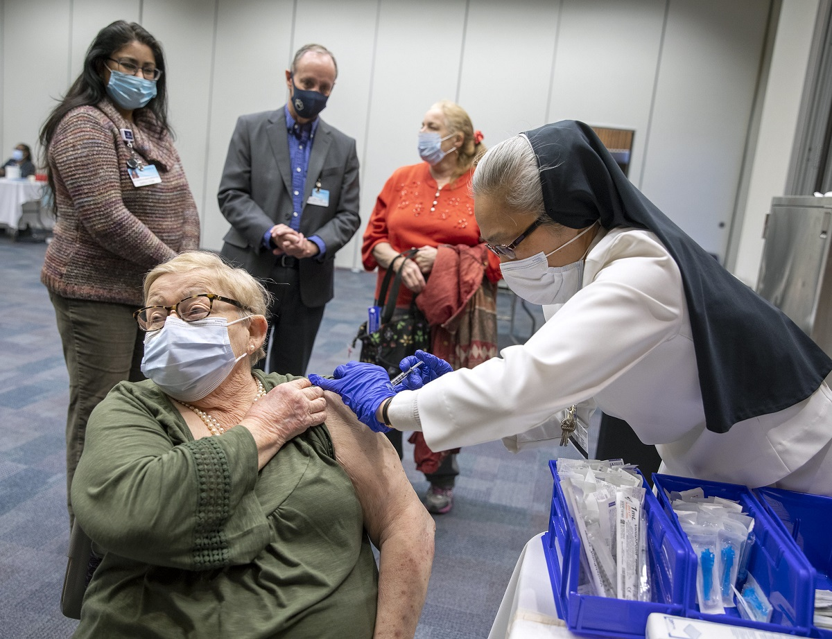 A woman in a mask looks away as another woman in hospital scrubs, rubber gloves and a nun's habit gives her in an injection into her shoulder.