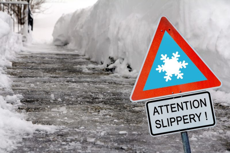 An icy sidewalk in winter with a sign in the foreground reading 'Attention slippery!'