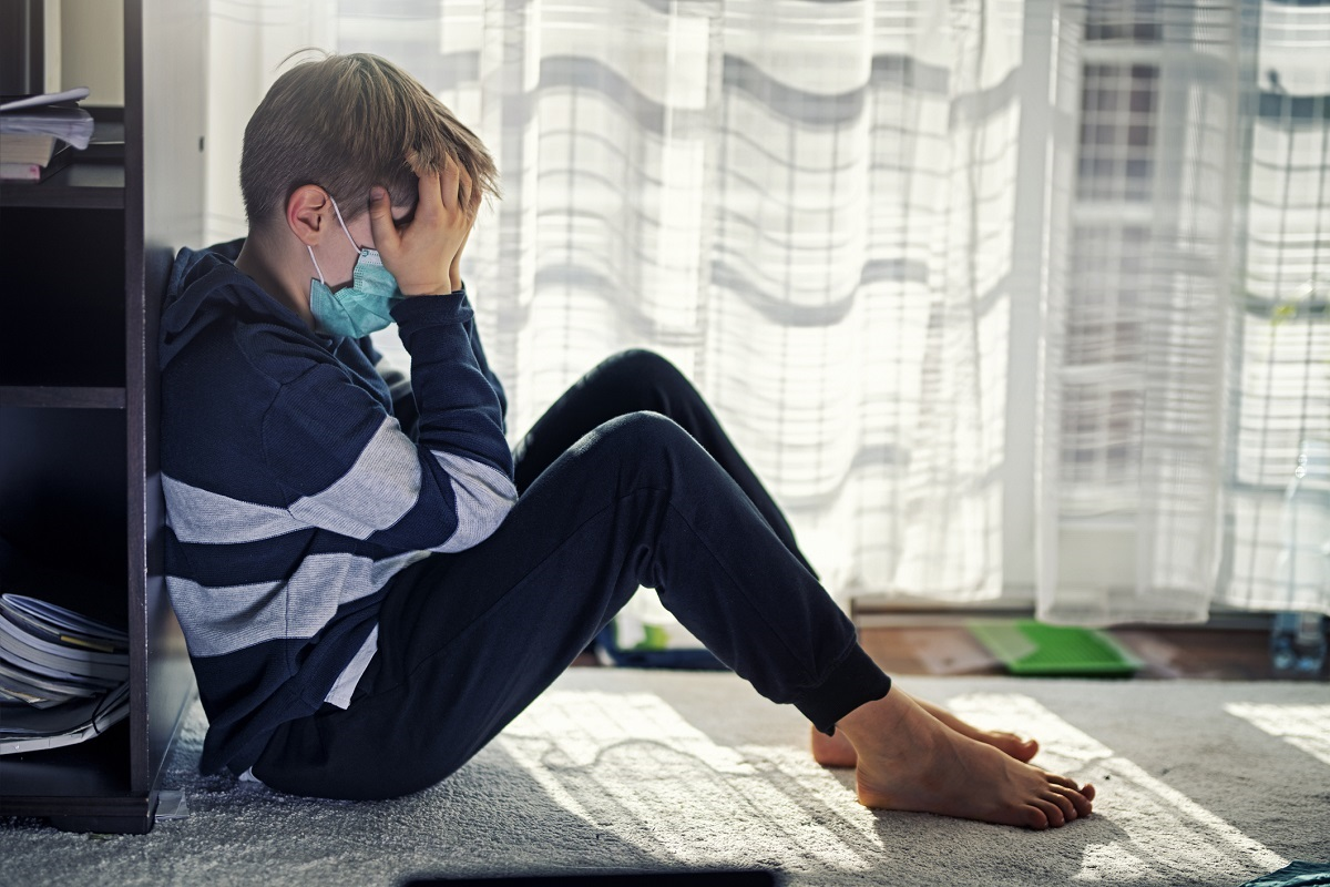 A young boy sits by a window, wearing a surgical mask, with his face in his hands.