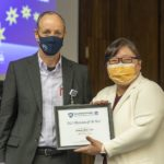 A man dressed in a gray suit and white shirt and wearing a navy blue face mask stands with a woman dressed in a while coat and dark blouse, and wearing glasses and an orange face mask, while holding a framed award.