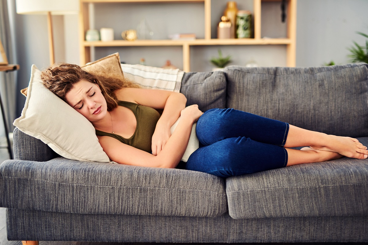 A woman in pain lies on her side on a couch pressing a cushion to her midsection.