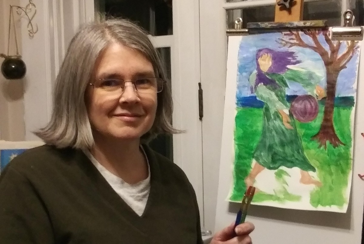 Jennifer Rudolph, who wears glasses and a V-neck sweater, sits at an easel and holds a brush in her hand. A painting on the easel shows a girl standing by a tree with her hair blowing in the wind.