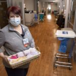 A woman in a mask stands in a clinic hallway with stained-wood floors holding a basket of feminine hygiene products.