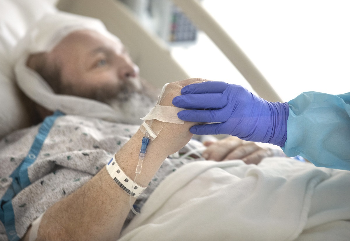 A male patient wearing a white and blue hospital gown reclines in a hospital bed. A nurse's hand, covered in a blue glove, grasps his hand, helping him to move.