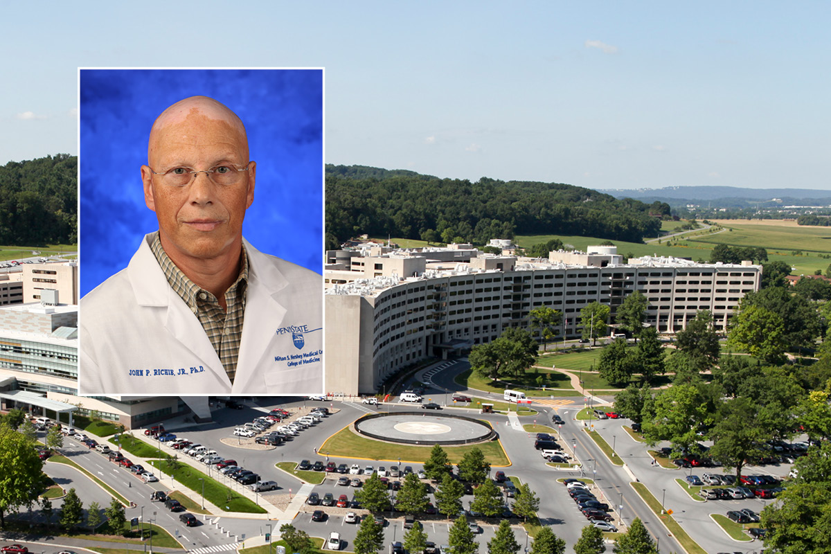 A head and shoulders professional portrait of John Richie against a background photo of Penn State College of Medicine