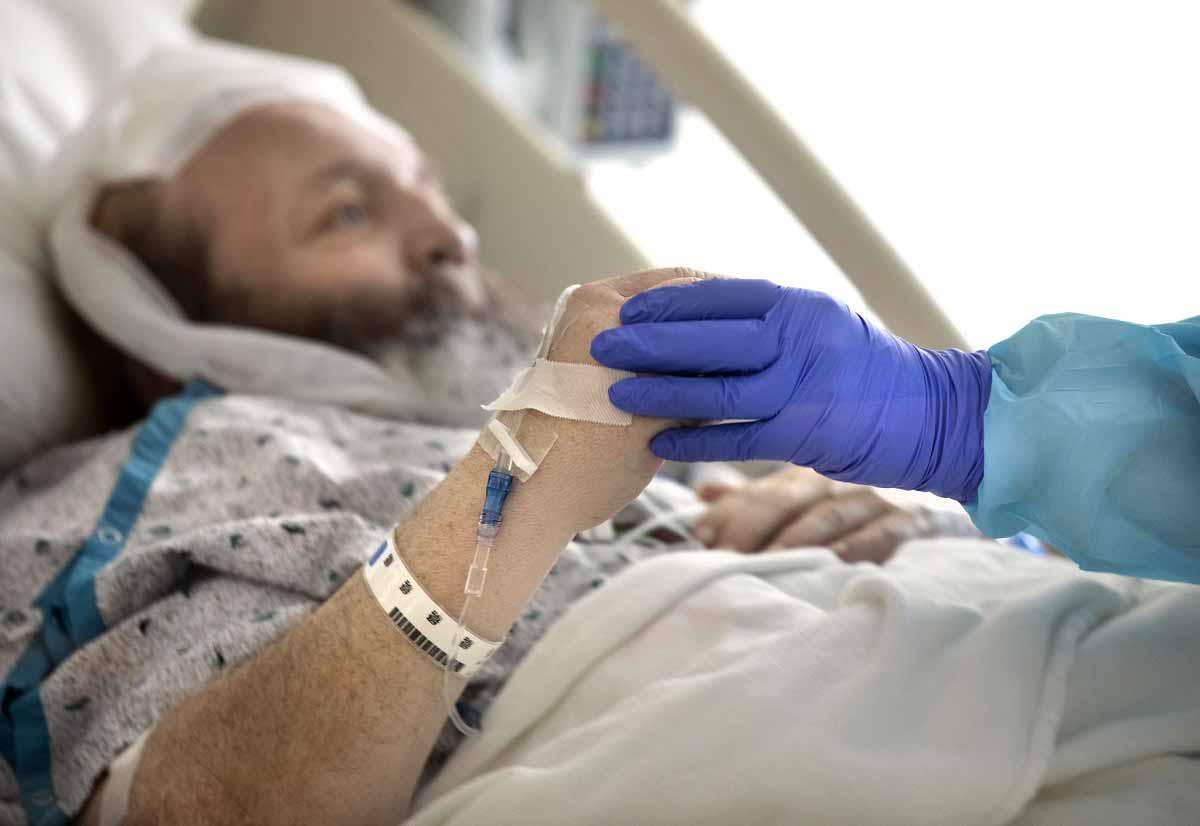 Un paciente masculino con una bata de hospital blanca y azul se reclina en una cama de hospital. La mano de una enfermera, cubierta con un guante azul, agarra su mano, ayudándole a moverse.