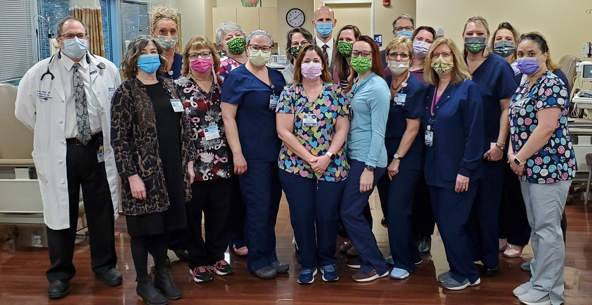 A group of health care workers in scrubs stand in a hospital room and pose for a photo.