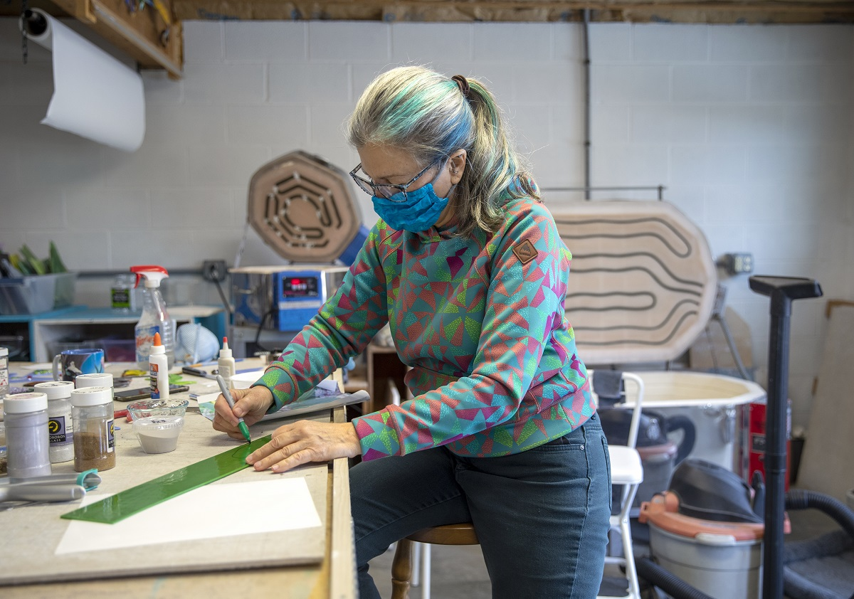 Linda Billet perches on a stool in her workshop and draws with a marker on a strip of glass. She wears glasses and a face mask and has her hair in a ponytail streaked with colors. Art supplies surround her on the counter where she works.