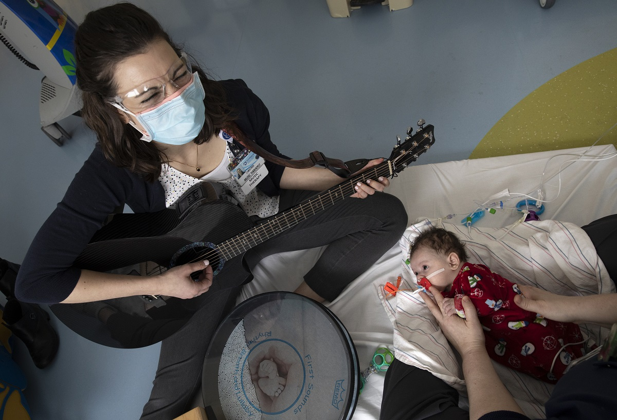 Tina Myers, who wears a mask and goggles, sits on the edge of a mattress on the floor and plays her guitar for a baby who is lying on the mattress. The baby, who sucks on a pacifier, is wearing a sleeper with snowmen on it and is held by a pair of hands.