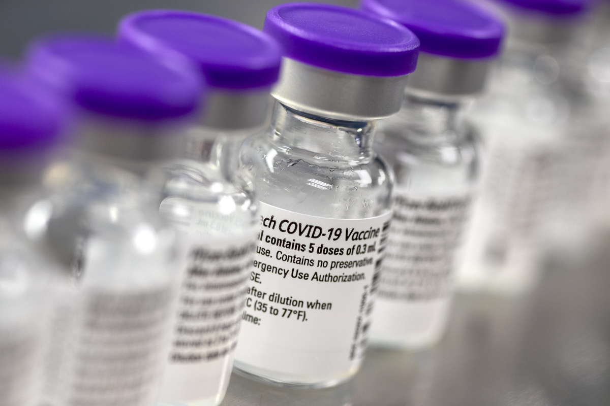 A close-up of several small bottles of COVID-19 vaccine, side by side.