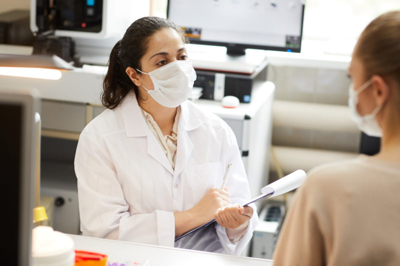 A doctor wearing a paper mask has a conversation with a clinical trial participant wearing a paper mask