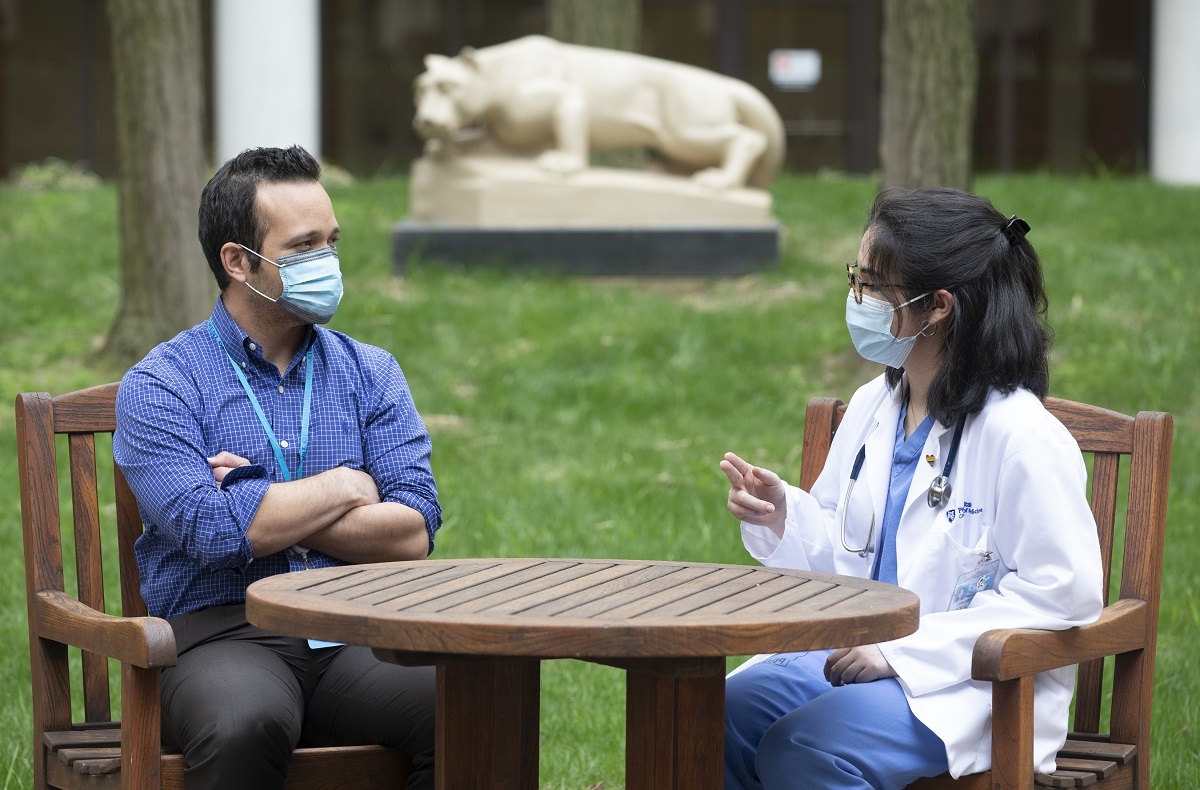 A man and woman sit outside at a wooden table with a statue of the Penn State Nittany Lion in the background. They both wear face masks and the woman is wearing glasses and hospital scrubs under a lab coat. The man's arms are crossed.