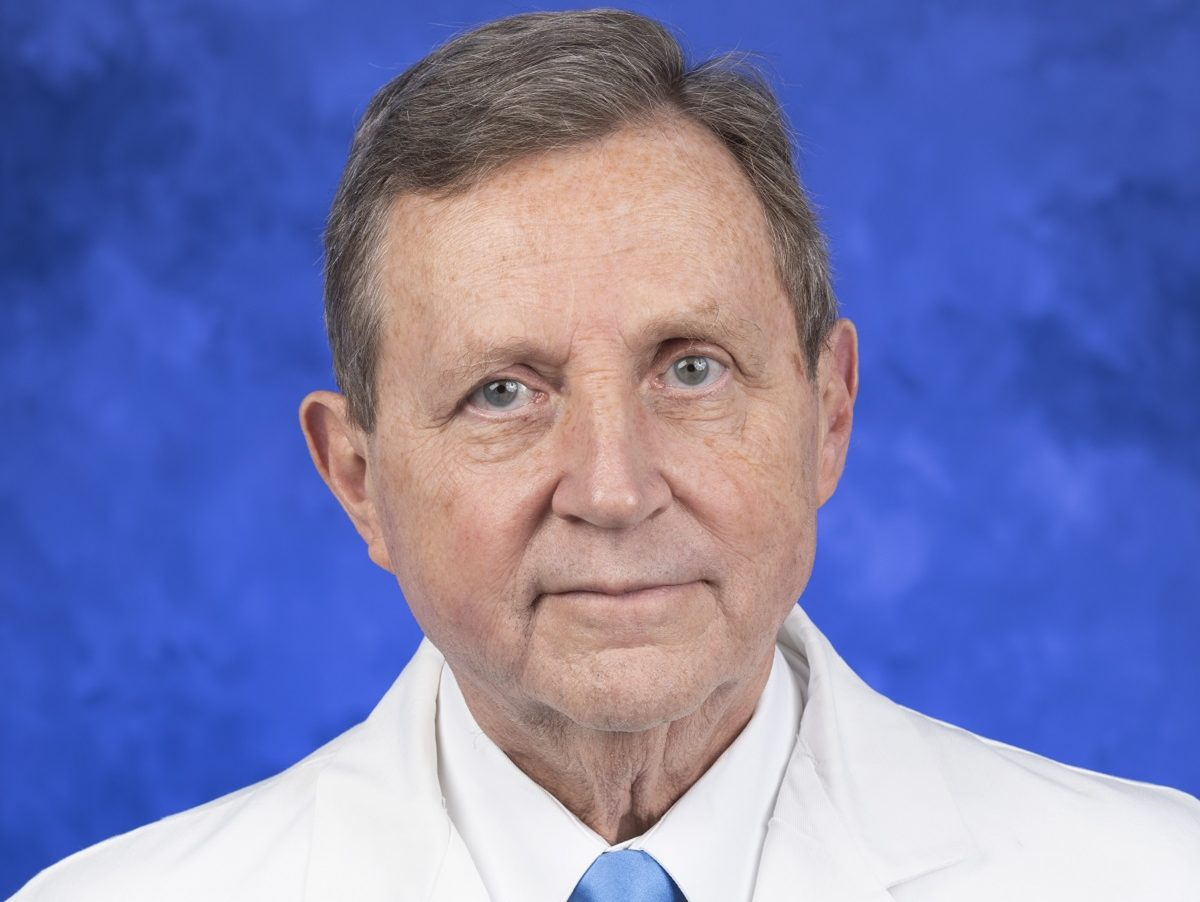 Dr. Robert Harbaugh with Penn State Health Milton S. Hershey Medical Center is pictured in a head-and-shoulders professional headshot. He is wearing a dress shirt, tie and lab coat embroidered with the Penn State logo.
