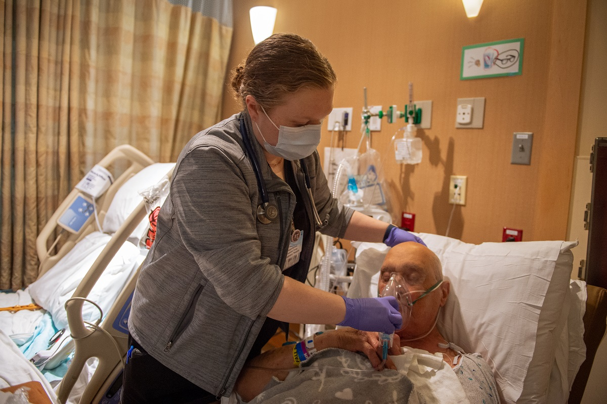 Margaret McGinnis, a respiratory therapist with Penn State Health St. Joseph, holds an oxygen mask to the face of a male patient who is lying in bed with his eyes closed. McGinnis is wearing scrubs, a sweat jacket, a lanyard with a nametag and a face mask. Behind her is another hospital bed.