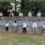 "Medical school students wearing white physician coats stand and sit around a gray, stone wall with the words ""Penn State University"" carved into it. A row of trees stand in the background."