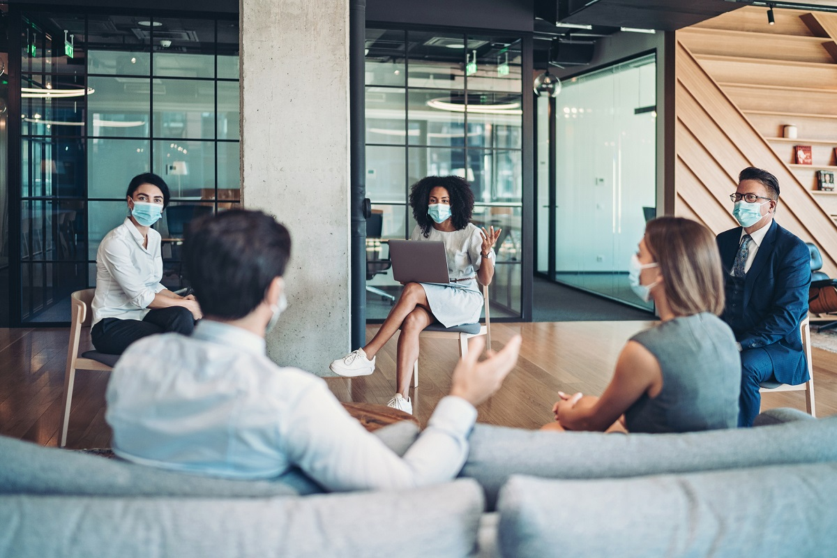 Five people in masks and business attire conduct a meeting in an office building.