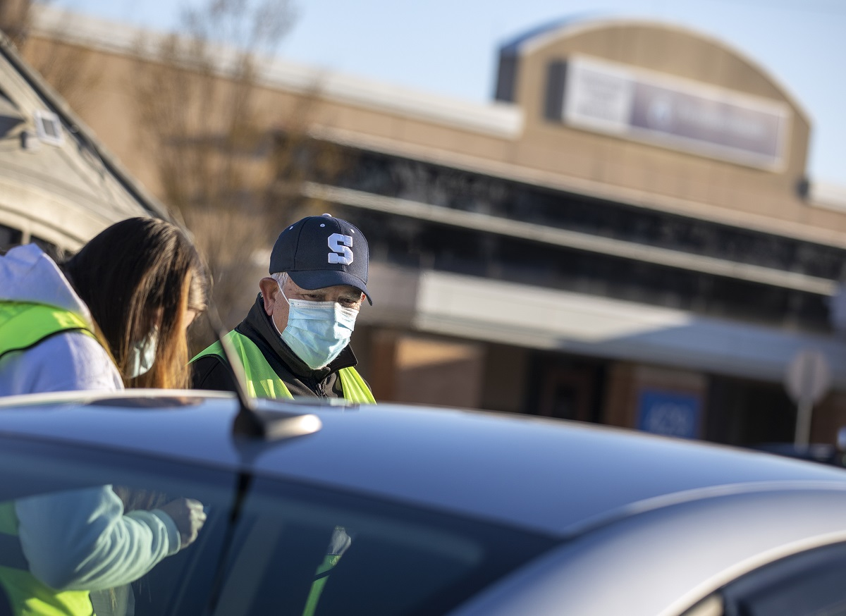A man in a ball cap with an S on the front and a surgical mask stands next to a woman in a mask and a hoodie, partially obscured by a car.