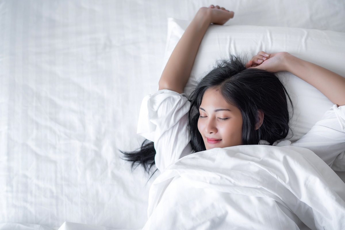 Young woman wakes up happy with a smile on her face in bed in the morning.