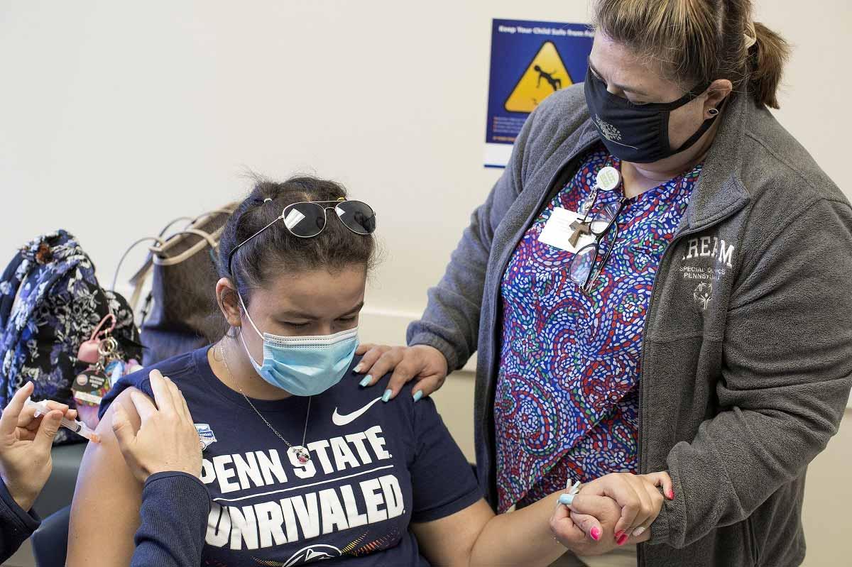Rachel Frometa, sentada y llevando una máscara y gafas de sol en la parte superior de la cabeza, sostiene la mano de su madre, Betty Frometa, quien está a su lado, mientras una vacuna está inyectada en su brazo por las manos de un trabajador de salud.