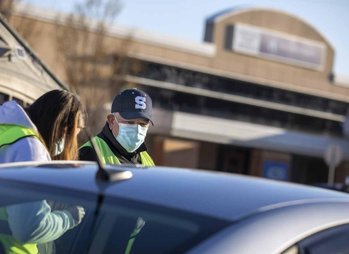 Un hombre con una gorra de béisbol con una S en la parte delantera y una máscara quirúrgica se para junto a una mujer con una máscara y una sudadera con capucha, parcialmente oscurecida por un auto.