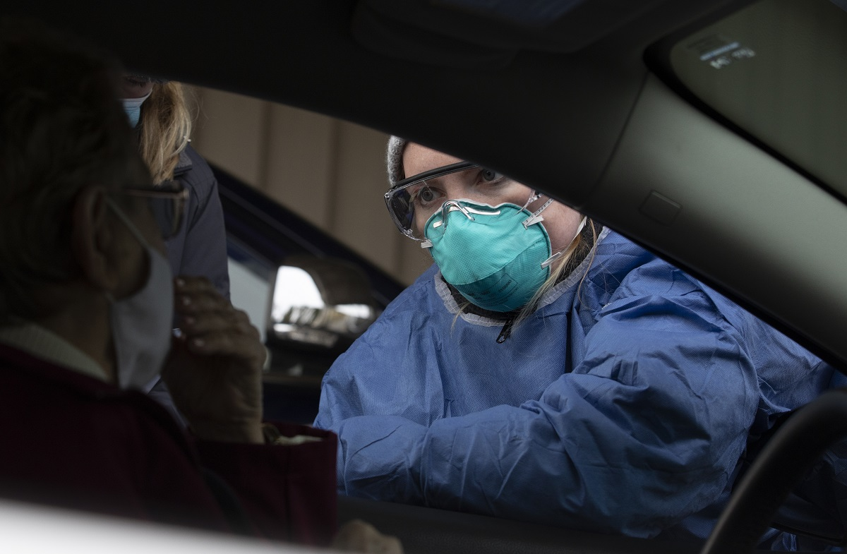 A nurse wearing a face mask gives instructions at a drive-thru COVID-19 testing site