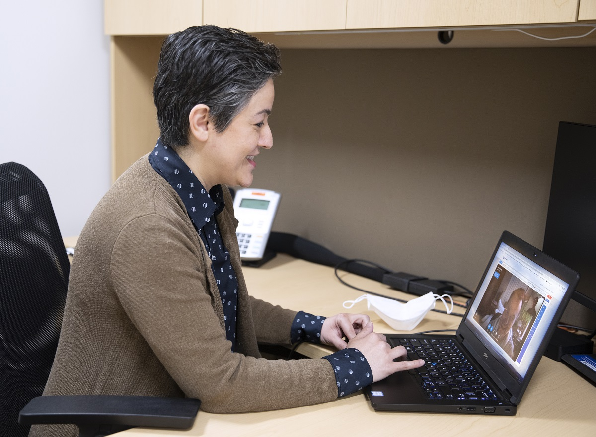 Female physician in sweater and dress shirt sits at a computer and smiles while talking with a patient during a telehealth visit.