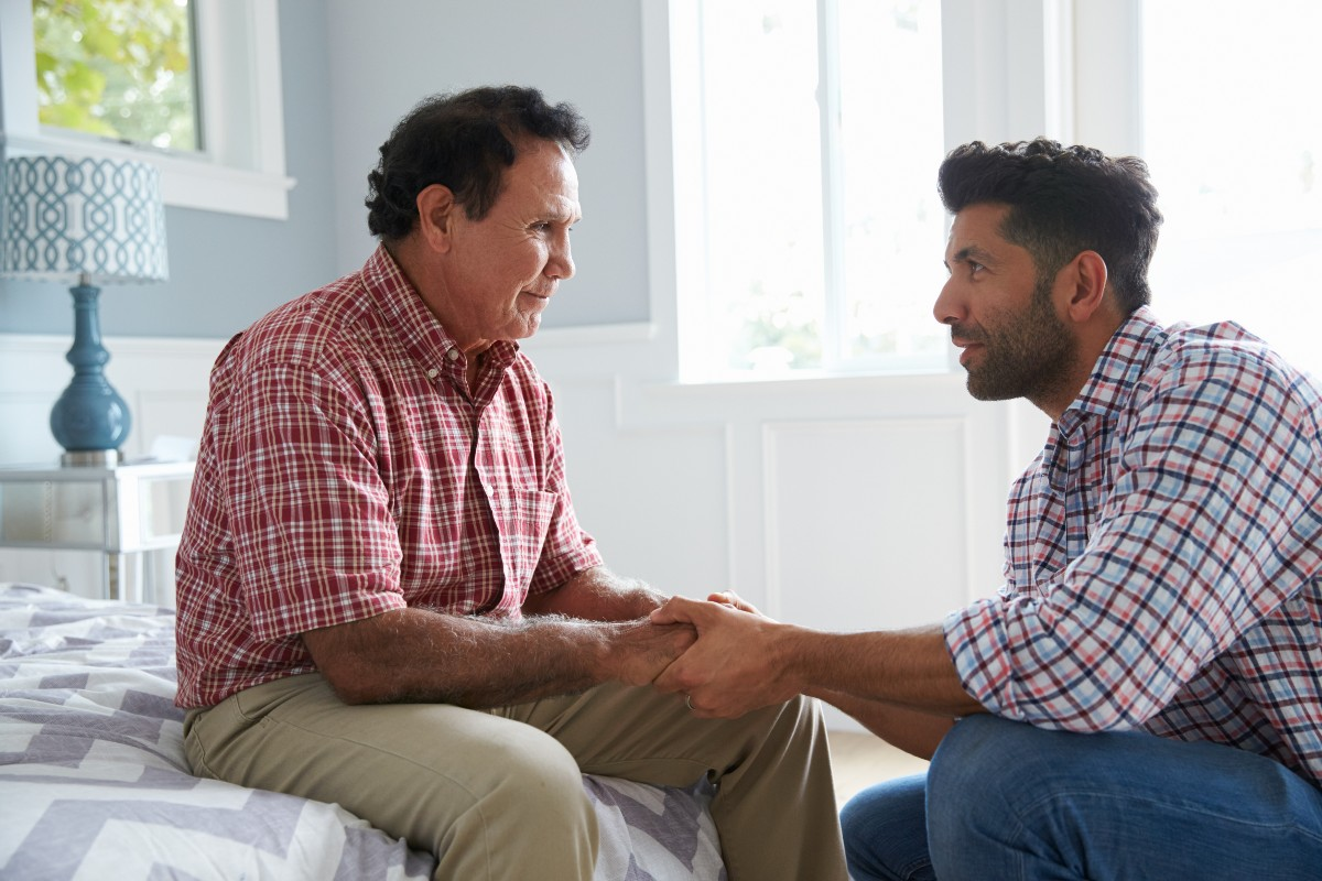 An adult son has a conversation about end-of-life care with his aging father.