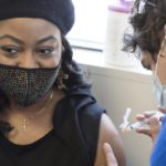 Tamika Washington, who wears a jeweled face mask, a cross necklace and a beret, looks away from her bare arm as a health care worker prepares to insert a syringe filled with the COVID-19 vaccine.