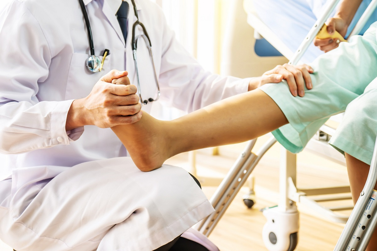 A doctor touches a patient's foot and knee during an exam. The doctor is wearing a white coat and a stethoscope. The patient is wearing short pants. Their faces are not visible.