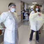 Two women don personal protective equipment in a hospital hallway.