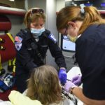 Paramedic Sarah Fishburne, who has short hair with glasses on top of her head and wears a face mask, and EMT Madigan Anderson, who has her hair in a ponytail and wears glasses and a face mask, sit in an ambulance with a patient on a stretcher, who is seen from behind. Medical equipment surrounds the patient.